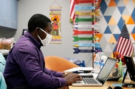 Teaching assistant Samuel Lavi helps out with an online class at the Valencia Newcomer School, Tuesday, Sept. 2, 2020, in…