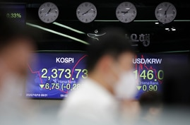 Currency traders watch computer monitors near screens showing the Korea Composite Stock Price Index (KOSPI), left, and the…