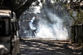 A Kashmiri protester throws an exploded tear smoke shell on government forces during a clash following the killing of two…