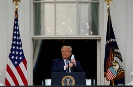 President Donald Trump removes his face mask to speak from the Blue Room Balcony of the White House to a crowd of supporters,…