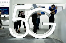 Visitors wearing mask to protect from the coronavirus walk past a 5G sign at the China Beijing International High Tech Expo in…
