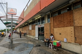 A woman waits for clients outside a supermarket with its windows covered with plywood as Tropical Storm Zeta approaches Cancun,…