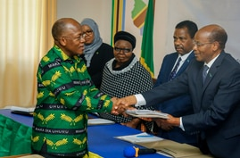 FILE - In this Tuesday, Aug. 25, 2020 file photo, President John Magufuli, left, who seeks a second five-year term, hands over…