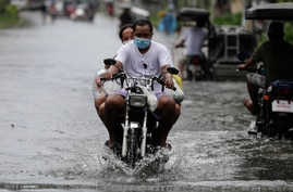 Residents on a motorcycle negotiate a flooded road due to Typhoon Molave in Pampanga province, northern Philippines, Monday,…