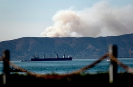 Seen from Alameda, Calif., a grass fire burns in South San Francisco on Friday, Oct. 16, 2020. Portions of Northern California…