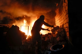 People try to remove car tyres from a car shop on fire after shelling by Azerbaijan's artillery during a military conflict in…