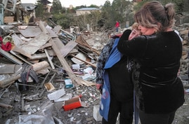 A neighbour comforts home owner, Lida Sarksyan, left, near her house destroyed by shelling from Azerbaijan's artillery during a…