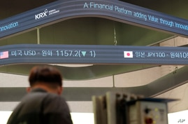 A man stands near a screen showing the foreign exchange rates at the Korea Exchange in Seoul, South Korea, Thursday, Oct. 8,…