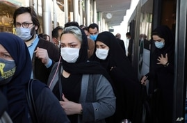 FILE - In this Sunday, Oct. 11, 2020 file photo, people wear protective face masks to help prevent the spread of the…
