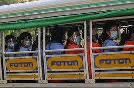 Factory workers wearing protective face masks and shields ride a truck as they go to their works in Hlaing Tharyar Industrial…