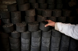 A man stocks up coal briquettes at his court yard, as many people living in old houses still rely on coal fire to heat up in…