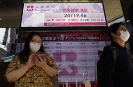 People walk past a bank's electronic board showing the Hong Kong share index at Hong Kong Stock Exchange Tuesday, Oct. 27, 2020…