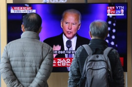 People watch a TV screen showing the broadcast of President-elect Joe Biden speaking, at the Seoul Railway Station in Seoul,…