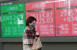A woman walks by an electronic stock board of a securities firm in Tokyo, Tuesday, Nov. 10, 2020. Asian stock markets rose for…