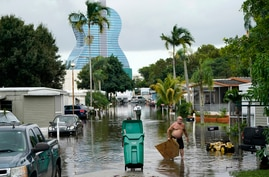 Residents clear debris from a flooded street in the Driftwood Acres Mobile Home Park in the shadow of the Guitar Hotel at…