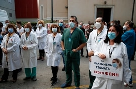 Health workers wearing face masks to protect against the spread of the coronavirus, take part in a protest at Evangelismos…
