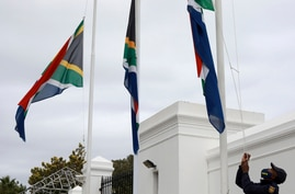 A policeman adjusts South African flags to half-mast outside parliament in Cape Town, South Africa, Wednesday, Nov. 25, 2020…