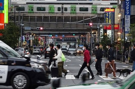 People walk along a pedestrian crossing Tuesday, Nov. 3, 2020, in Tokyo. The Japanese capital confirmed more than 200 new…