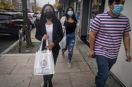 Emili Prado, 21, left, legal liaison for La Colmena, a community-based organization working with immigrant workers, walk with…