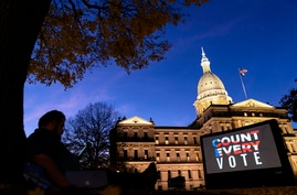 "The phrase ""Count Every Vote"" is projected on a giant screen organized by an advocacy group in front of the State Capitol while…"