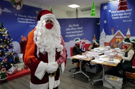 """A postal worker dressed as Santa, talks with co-workers who call themselves """"Elves"""" as they open envelopes addressed to """"Pere…"""
