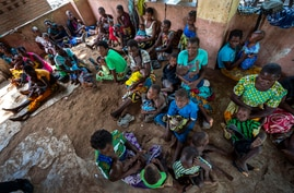 FILE - In this Dec. 11, 2019 file photo, residents of the Malawi village of Tomali wait to have their young children…