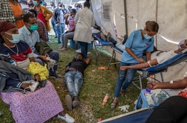 A man lies down after giving blood at a blood drive in support of the country's military, at a stadium in the capital Addis…