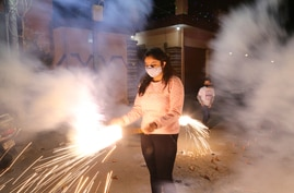 A girl plays with fireworks during Diwali, the Hindu festival of lights, in Jammu, India Saturday, Nov. 14, 2020. More than a…