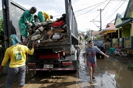 Workers collect garbage along a mud-covered road after floodwaters caused by Typhoon Goni rose inside their village in Batangas…