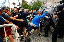 Soccer fans waiting to see Diego Maradona lying in state clash with police outside the presidential palace in Buenos Aires,…
