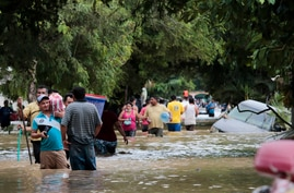 Residents walk past inundated vehicles in the flooded streets of Planeta, Honduras, Friday, Nov. 6, 2020, in the aftermath of…