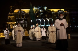 Priests walk towards Lima's Cathedral before the start of a Mass dedicated to the more than 30,000 deceased in Peru due to…