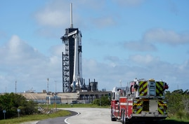 NASA firefighters drive on the road outside the fence near a SpaceX Falcon 9 rocket, with the company's Crew Dragon capsule…