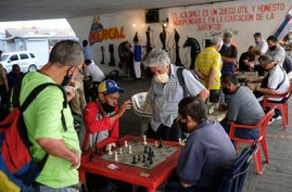 Men wearing masks play chess under a bridge in Caracas, Venezuela, Saturday, Dec. 26, 2020, amid the new coronavirus pandemic. …