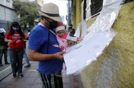 A man holding his infant daughter checks a voting list in the elections to choose members of the National Assembly, in Caracas,…