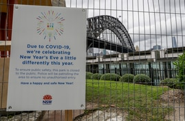 A signs adorns a security fence near the harbour foreshore ahead of New Years Eve in Sydney, Australia, Thursday, Dec. 31, 2020…