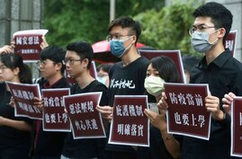 """Hong Kong students and Taiwanese supporters hold slogans reading: """"Evil law under the pressure of the border, Work hand in hand…"""