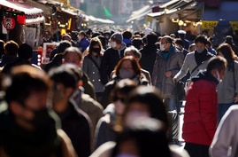 People wearing face masks to protect against the spread of the coronavirus walk though a shopping street Thursday, Dec. 31,…