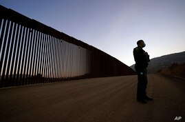 Border Patrol agent Justin Castrejon speaks in front of newly replaced border wall sections Thursday, Sept. 24, 2020, near…