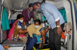 A patient is assisted by others to get down from an ambulance at the district government hospital in Eluru, Andhra Pradesh…