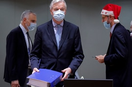 A colleague wears a Christmas hat as European Union chief negotiator Michel Barnier, center, carries a binder of the Brexit…