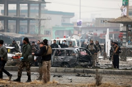 Afghan security personnel inspect the site of a bombing attack in Kabul, Afghanistan, Sunday, Dec. 20, 2020. The strong car…