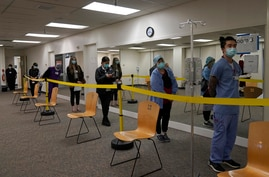 Healthcare workers wait in line to receive the Pfizer-BioNTech COVID-19 vaccine at Seton Medical Center in Daly City, Calif.,…