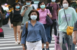 People wearing face masks to protect against the spread of the coronavirus cross and intersection in Taipei, Taiwan, Friday,…