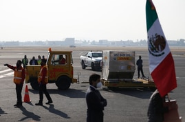 The first shipment of the Pfizer COVID-19 vaccine to Mexico is transported on the tarmac after being unloaded from a DHL cargo…