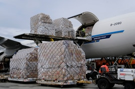 FILE - In this April 10, 2020, file photo, a ground crew at Los Angeles International Airport unload pallets of medical…