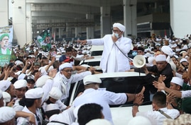Indonesian Islamic cleric and the leader of Islamic Defenders Front Rizieq Shihab, center, speaks to his followers upon arrival…