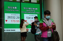 People wearing face masks to protect against the coronavirus stand in front of a bank's electronic board showing the Hong Kong…