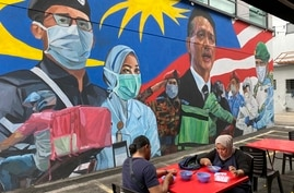 A Malay couple have lunch next to a graffiti tribute to Malaysian workers on the frontlines against the COVID-19 coronavirus at…