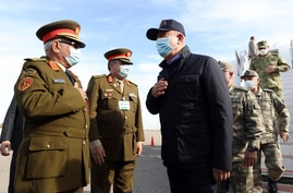 Turkey's Defense Minister Hulusi Akar, centre, and other top Turkish military commanders, right, greet Libyan commanders, at…